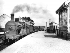 Ballyshannon G.N.R. station in 1956 one year before closure. Passengers are being checked in the background by Irish Customs. Buildings on right include waiting shelter and signal cabin.