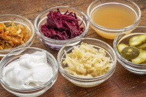 A sampler of fermented food great for gut health - glass bowls against wood:  kimchi, red beets, apple cider vinegar, coconut milk yogurt, cucumber pickles, sauerkraut