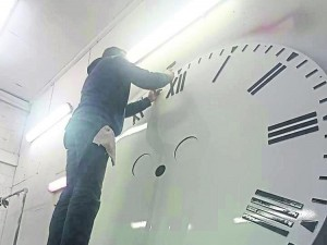 A hands-on approach - Cllr Barry Sweeny at work on the new clock face